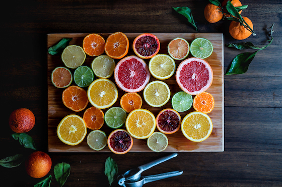 Multicolored citrus slices laid invitingly on a wooden cutting board