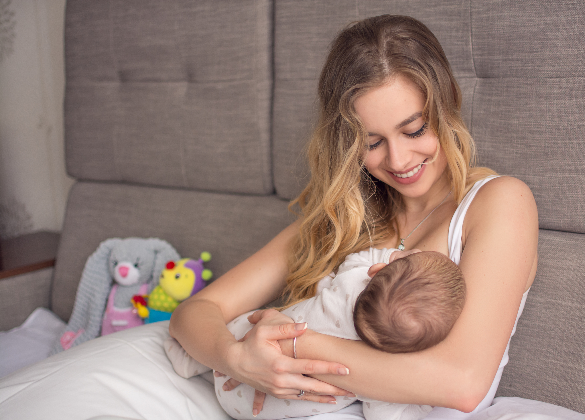 Young woman breastfeeds a newborn baby while she sits smiling.
