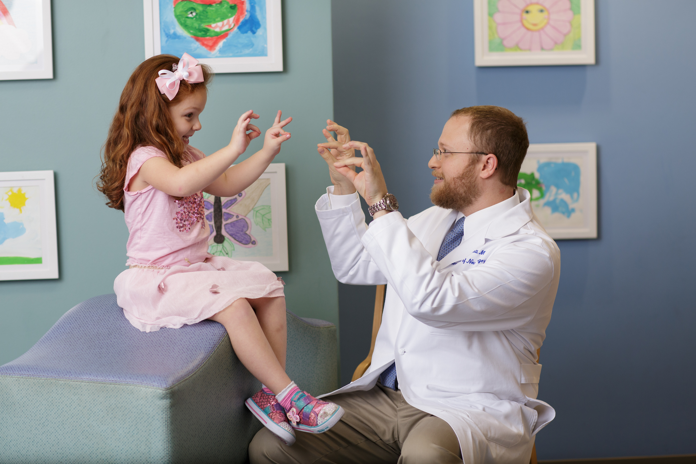 UF Health Children Hospital neurosurgeon makes a funny face with a young girl in a tutu.