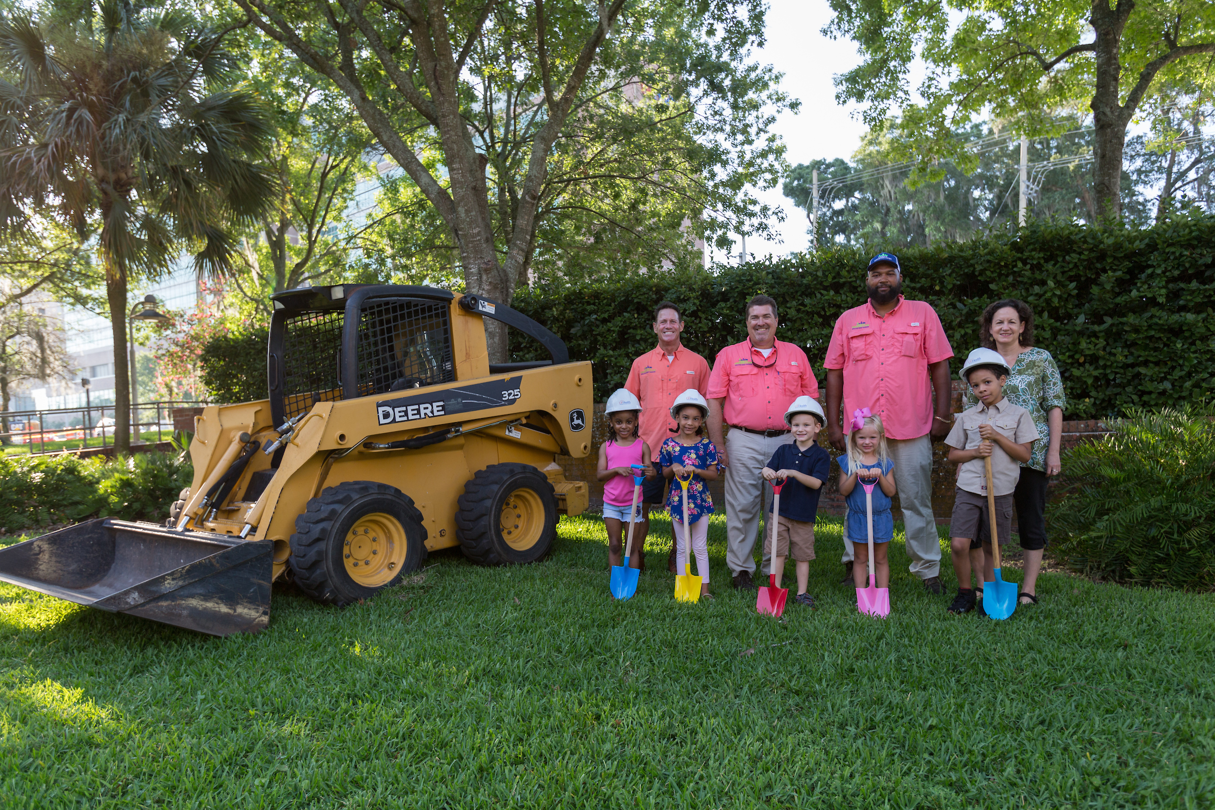 Children holding shovels and wearing hard hats in a garden with a bulldozer next to them and adults standing behind them.