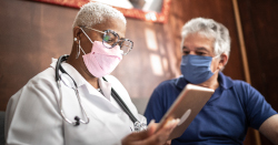 A woman wearing a white coat looks at a clipboard while a man wearing a blue shirt watches.