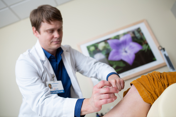 Integrative medicine doctor performs treatment on a patient at the University of Florida health.