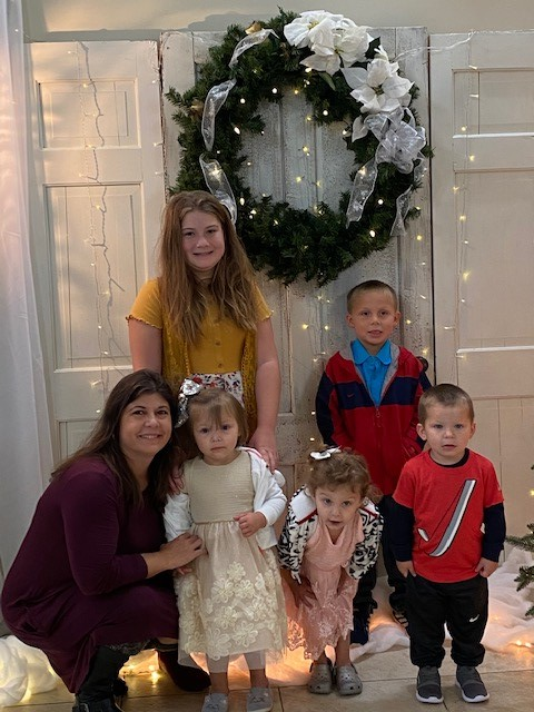Kim smiling at the camera with her daughter and grandchildren standing against a wooden door that features a Christmas wreath.