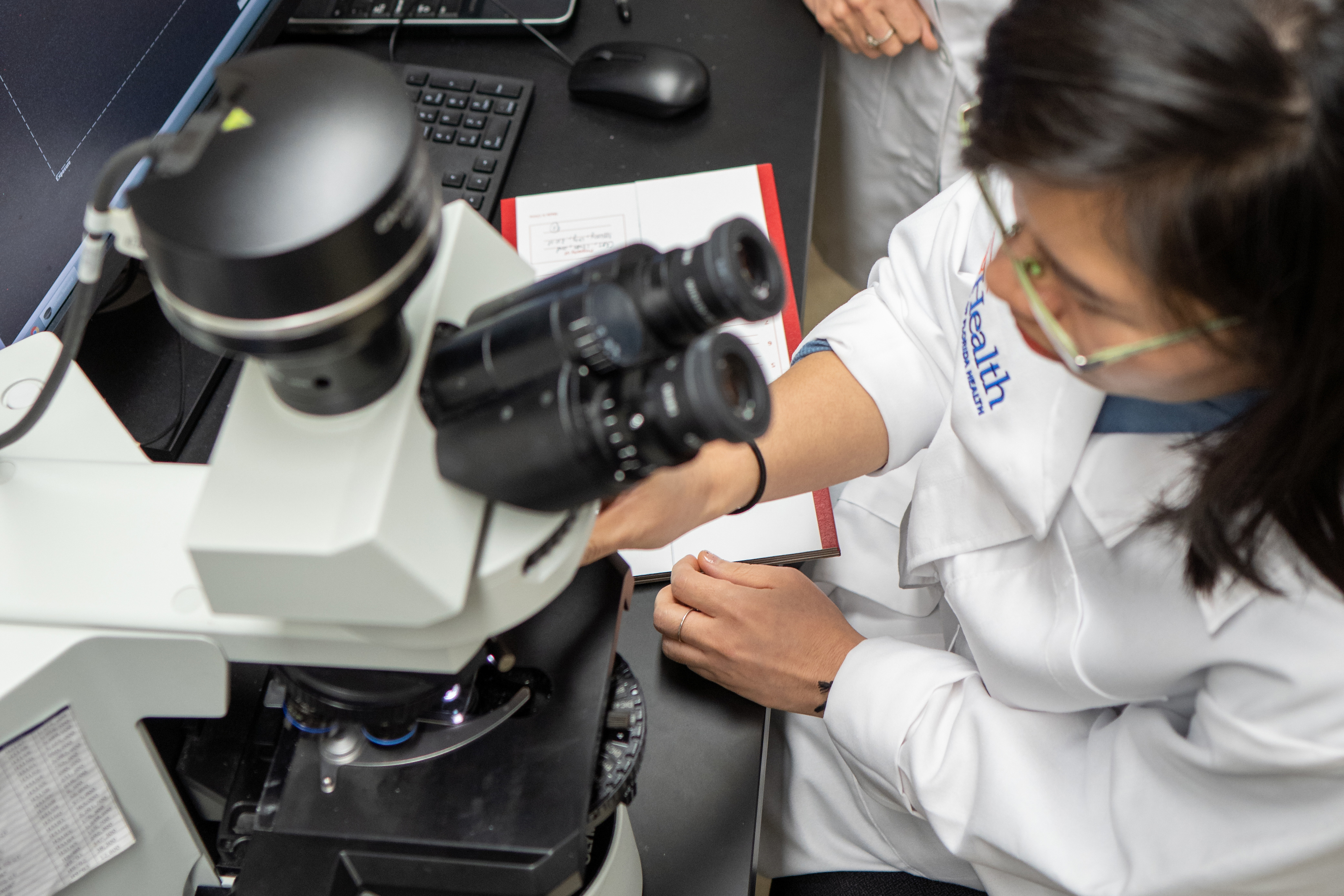 Researcher in lab at microscope