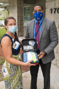 At a pair of socially distanced ceremonies on Sept. 29, Liz Warren of the UF Health PulsePoint task force presented John Alexander of Reichert House, pictured, and Tim Cannon of Alliance Credit Union with a pair of automated external defibrillators.