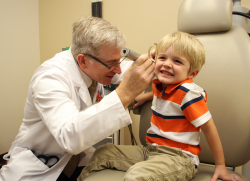Patrick Antonelli, M.D., co-author of a study showing quinolone ear drops appear to heighten the risk of a perforated ear drum, examines a patient.