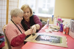 Noelle Hammer, founder of Art Without Boundaries, paints with Peggy Blitch, one of the many seniors at Al'z Place with Alzheimer's disease.