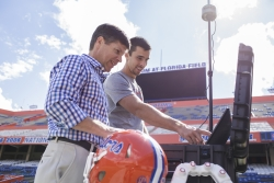 Dr. james Clugston and Matt Graham, coordinator for the head impact telemetry system at UF, set up the system inside Ben Hill Griffin Stadium. The HITS system allows team physicians to monitor hits players receive on the field using sensors placed inside their helmets.