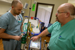Tim Bantle, R.R.T., left, along with Jeff Brown, ECMO Specialist, examine a portable ECMO machine that enables critically ill patients to be more easily transported to UF Health Shands Hospital. Photo credit: Jesse Jones