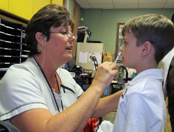 "A volunteer administers the ""flu mist"" to an Alachua County Elementary School student. Photo Credit: Jackie Johnson, public information officer for Alachua County Public Schools."