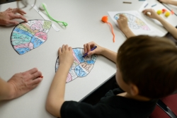 """A boy colors a """"brain hat,"""" which was used during an event to teach young students about the regions of the brain. The students visited the Evelyn F. and William L. McKnight Brain Institute of the University of Florida for a Brain Awareness Week event."""