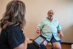 Dallas Graham, left, an Abbott representative, talks with Felix Favicchio as she activates his Proclaim XR neurostimulation system. Favicchio had the device implanted at UF Health in late September to ease his chronic back pain.  Credit: Louis Brems