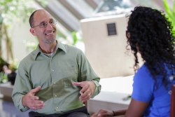 Joel Bialosky, Ph.D., a member of the research team, explains a treatment for pain to a patient. Photo by Mindy Miller