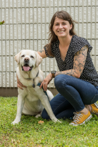 Third-year University of Florida veterinary student Maggie Smallwood is shown with her 7-year-old yellow Labrador retriever, named Leo. Leo received the first total ankle replacement surgical procedure performed on a dog in Florida in January at UF's Small Animal Hospital. (Photo by Louis Brems).
