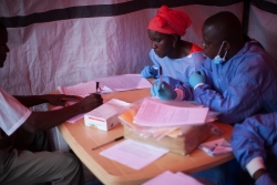 WHO/S. Hawkey-Nene Aminata Diallo and Gamou Saiman Gaston, from the World Health Organization Ebola vaccination team, carefully go through the consent process with a participant in the Ebola vaccine trial.