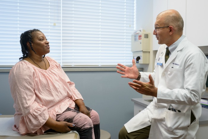 Borna Mehrad, M.D., chief of the UF College of Medicine's division of pulmonary, critical care and sleep medicine, talks to a patient recently at UF Health's interstitial lung disease clinic.