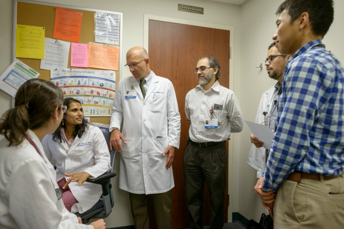 Borna Mehrad, M.D., chief of the UF College of Medicine's division of pulmonary, critical care and sleep medicine, meets with members of UF Health's interstitial lung disease team.