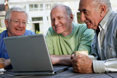 Three men sit gazing at a laptop computer.