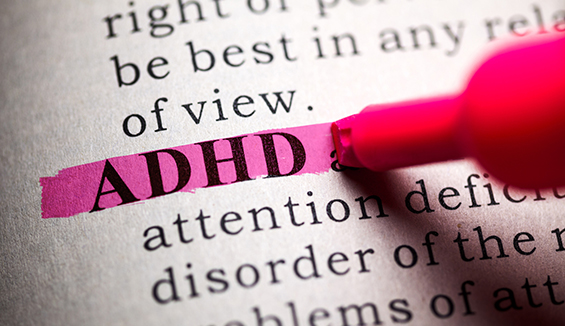 Highlighting the word ADHD in a book.
