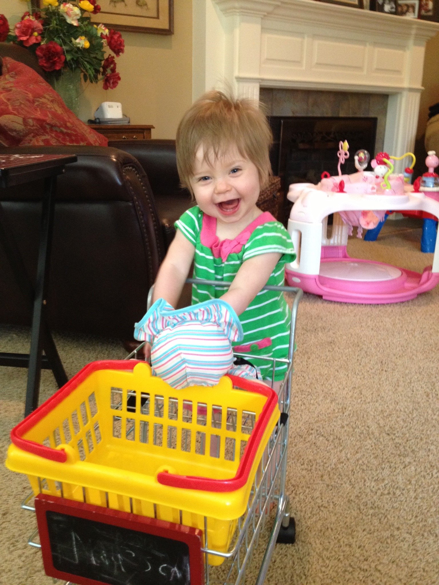 A smiling young girl pushes a toy plastic cart.