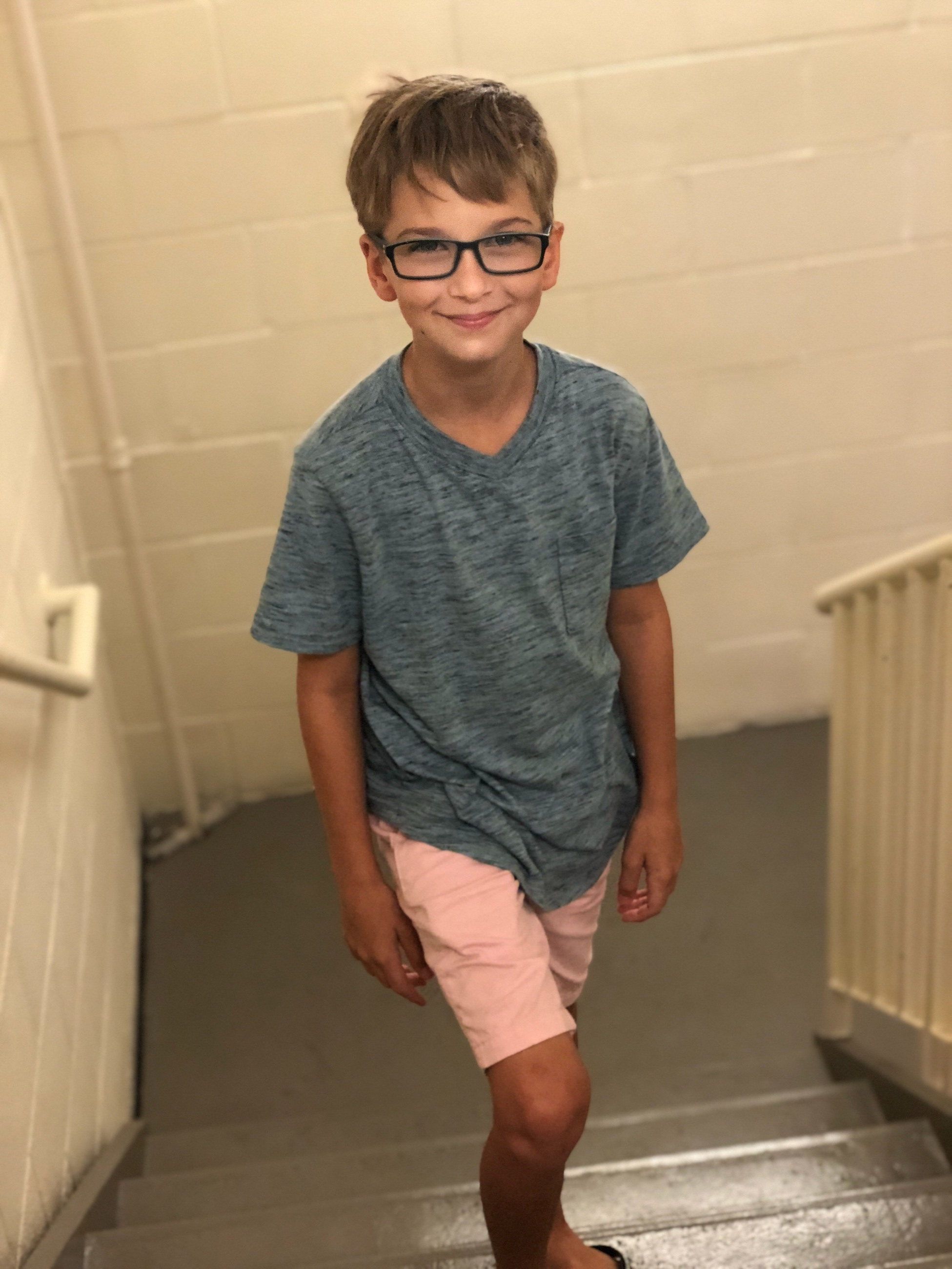 pediatric patient wearing glasses smiling standing on stairs