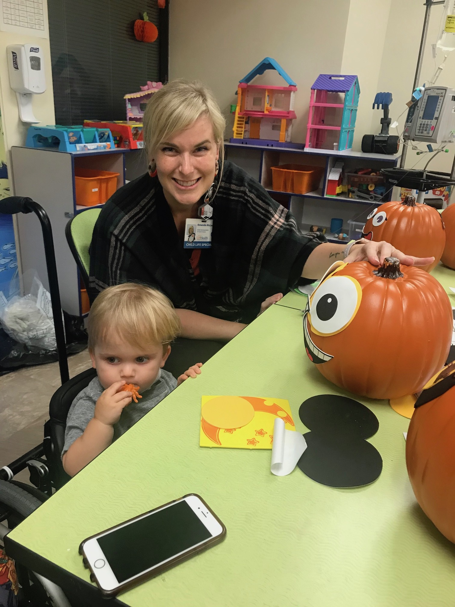 Child life staff member decorating a pumpkin with a pediatric patient