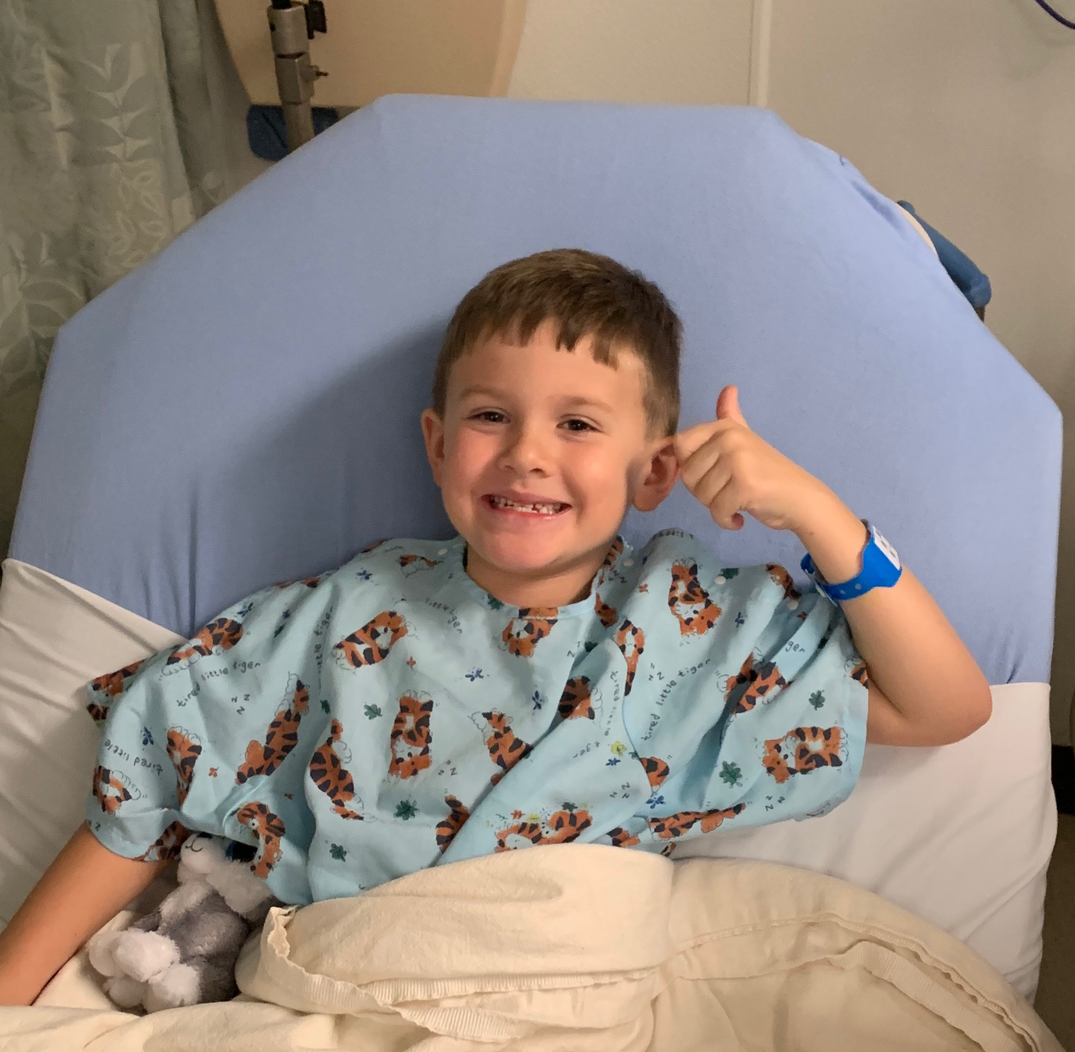 baylor in a hospital gown tucked into a hospital bed while smiling and holding a thumbs up