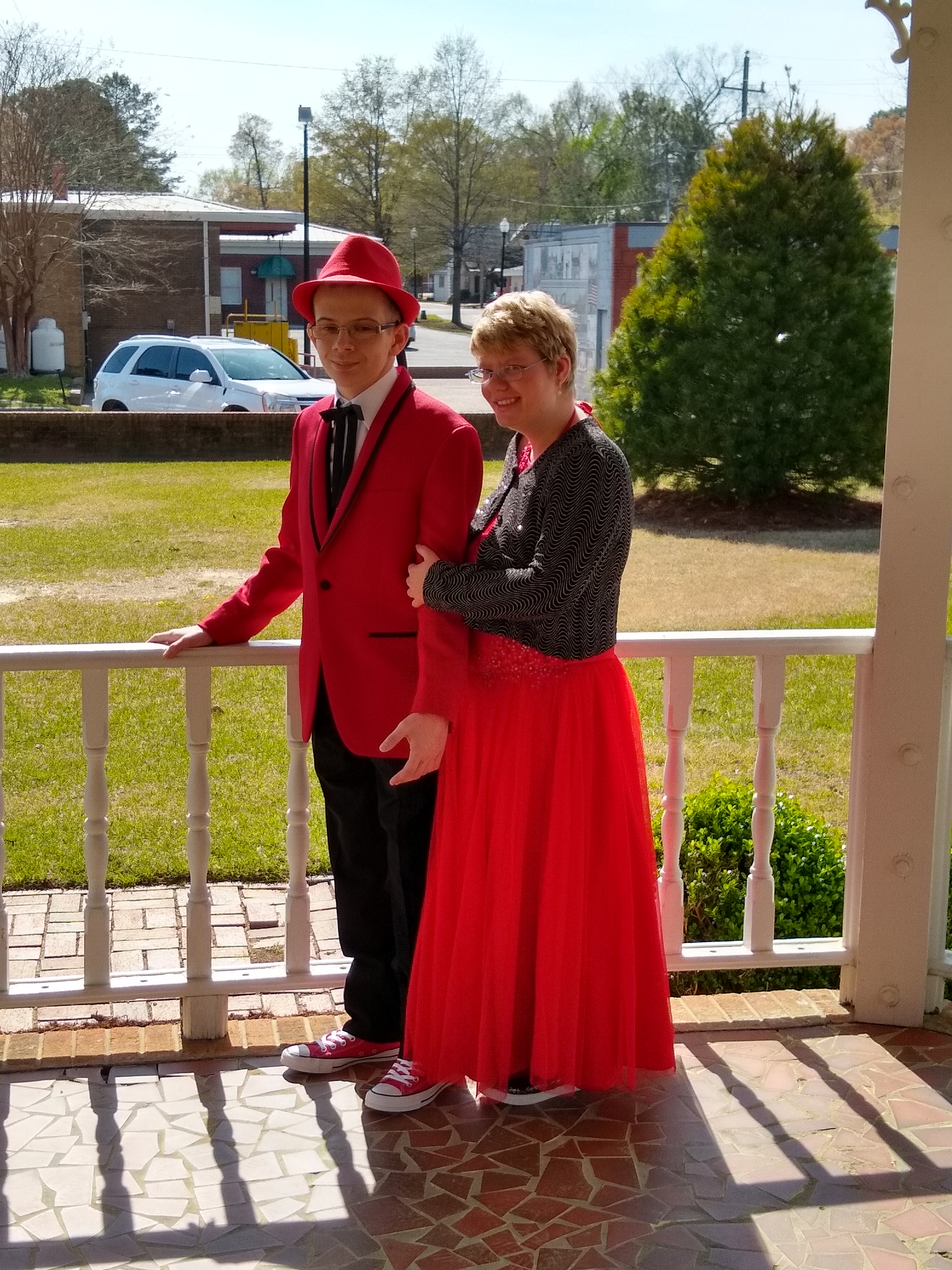 couple posing in matching red formal outfits to attend senior prom