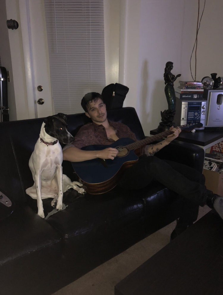 dylan lambert playing a guitar on a couch sitting next to a dog