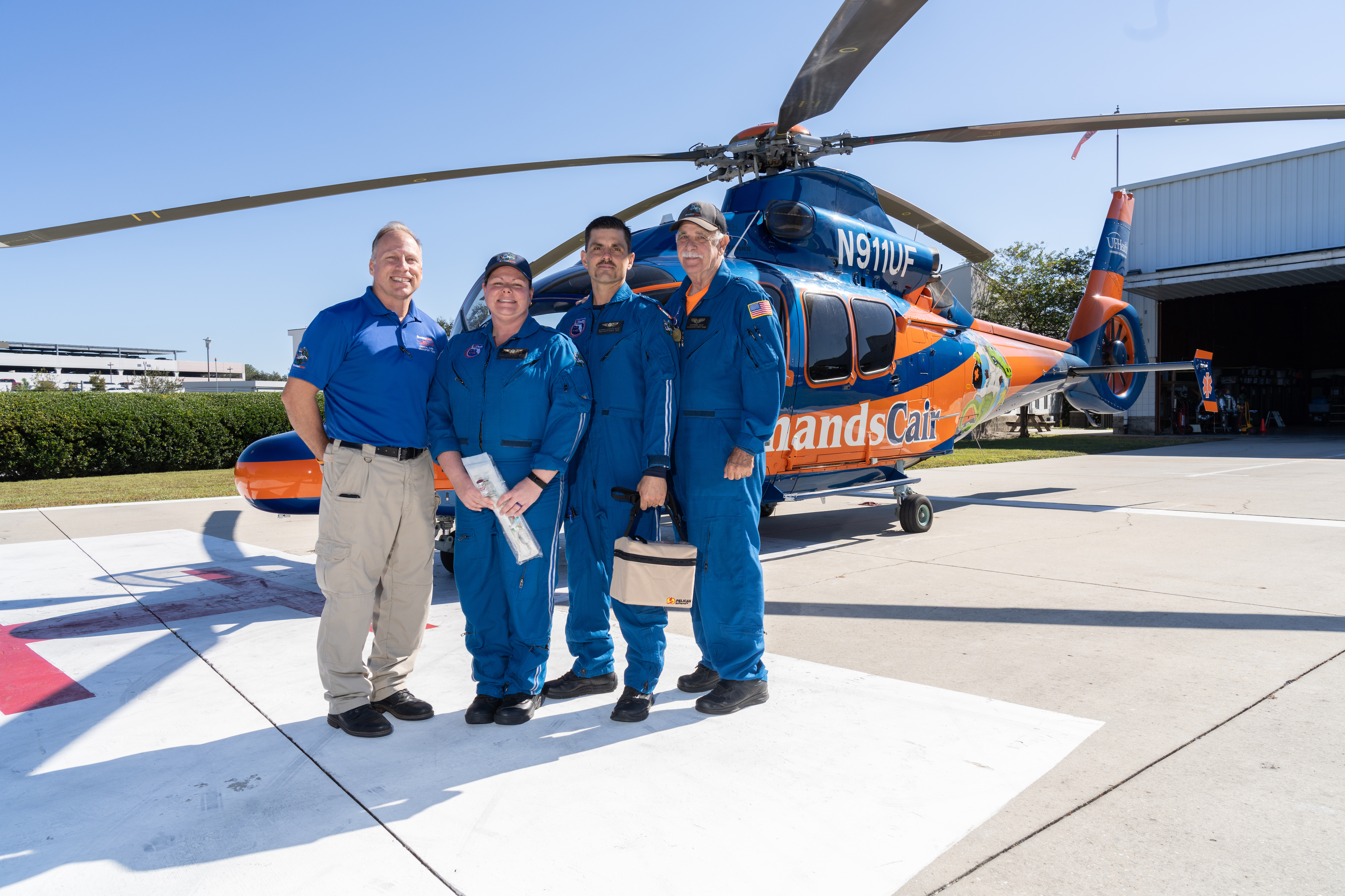 ShandsCair team of four people standing in front of a ShandsCair helicopter