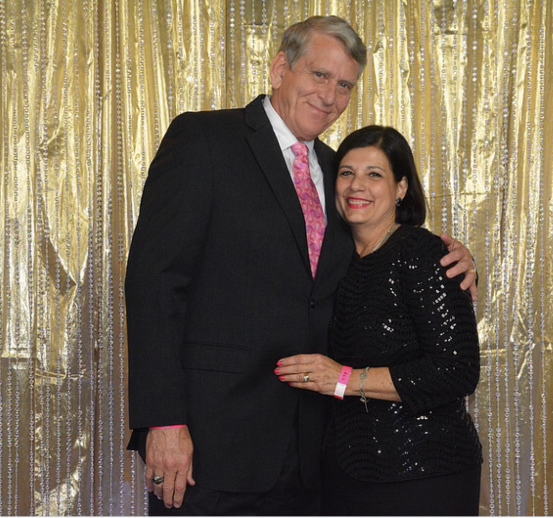 patient and his wife in formal wear posing in front of a gold backdrop