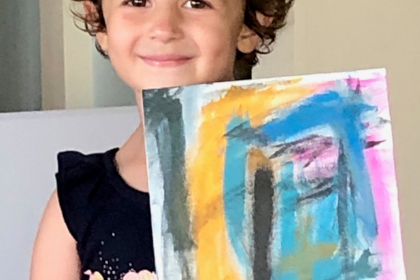 Josie Macchio poses with one of her paintings