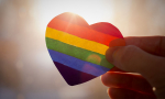 A hand hold up a transparent paper heart colored like a rainbow. The sun is shining through the heart.