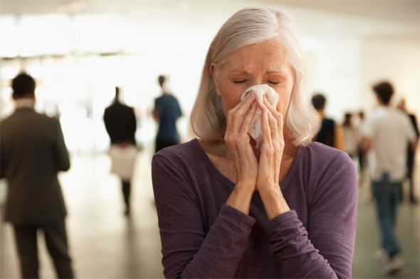 Woman sneezing in a crowded lobby.