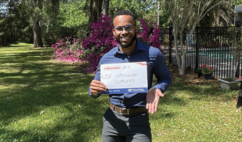 Akeem Bartley, a Black male student, stands in a field surrounded by trees and blooming azaleas. He's holding a sign that announces his number one match with USF's vascular surgery program.