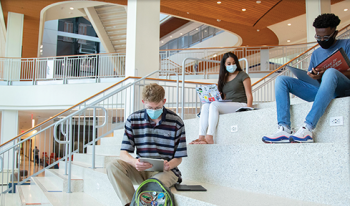 Three students sit on the steps of the Reitz Union. Each are wearing masks.