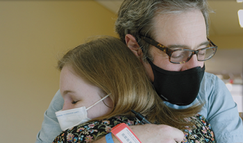 Rob Rushin, a T-cell lymphoma patient, hugs Sarah Wheeler, a clinical pharmacy specialist and member of his care team.