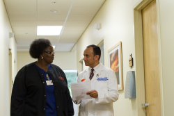 Nash Moawad, M.D., speaking with a fellow staff member.
