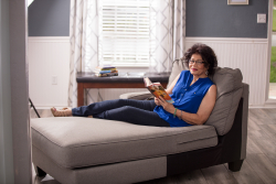 Gail sitting on the couch with a book.