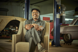 Jerry Nettles sits in a chair in a carshop