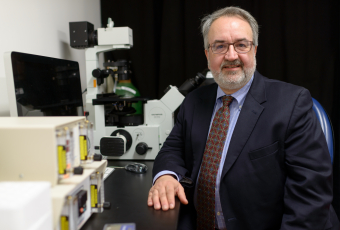Photo of Keith L. March, M.D., Ph.D. sitting next to a fancy microscope