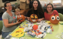 three children and an adult sitting at a table decorating pumpkins