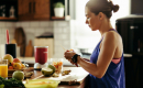 Woman in athletic clothing standing at a kitchen counter cutting fresh fruit for a smoothie