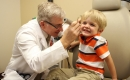 A photograph of a friendly, gray haired male doctor checking the right ear of a smiling, blond haired boy who is about five years old. Represents a new UF Health study questions the safety of antibiotic ear drops prescribed to children after ear tube surgery.