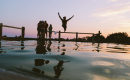 Beautiful sunset image featuring fun-loving, young adults at a lake with one young man leaping into the water with arms outstretched